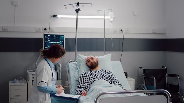 Beoefenaar arts die zieke man controleert die ziektebehandeling op klembord schrijft