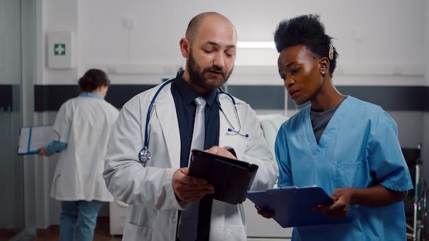 Beoefenaar arts met zwarte assistent die herstelbehandeling controleert