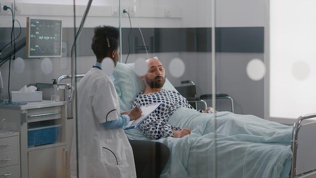 Beoefenaar-specialist met zwarte huid die zieke man controleert die ziektebehandeling schrijft