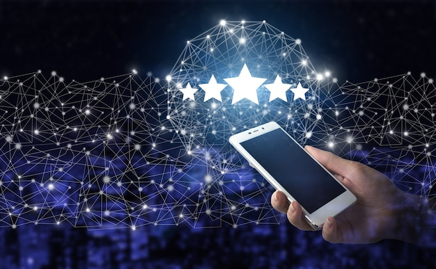 Beoordeling, beoordeling, tevredenheid. hand houden witte smartphone met digitaal hologram vijf sterren teken op de donkere onscherpe achtergrond van de stad. verhoog beoordeling of rangschikking, evaluatie en classificatieconcept.