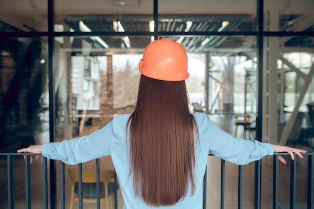 Beoordeling van het werk. vrouw met een oranje veiligheidshelm die met haar rug naar de camera staat en haar handen op het hek leunt om het werk binnenshuis te evalueren