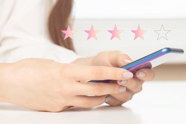 Beoordeling van kwaliteit via een smartphone. vrouwenhanden met een mobiele telefoon zetten sterren op het scherm in de app