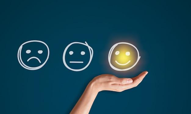 Beoordelingsconcept. vrouwenhand die gelukkige emotie van het glimlachgezicht kiezen