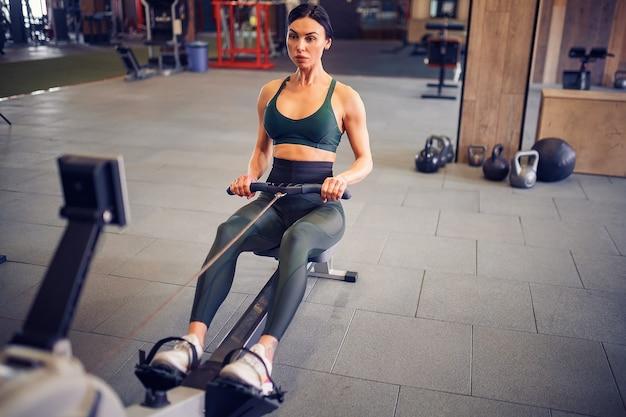 Bepaalde jonge vrouw die op rijmachine in gymnastiek uitwerkt