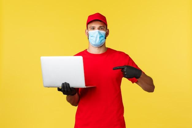 Bepaalde koerier in medisch masker en rood uniform, wijzend op laptop en kijk serieuze camera, gele achtergrond