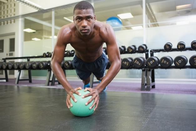 Bepaalde man doet push-ups met bal in de sportschool
