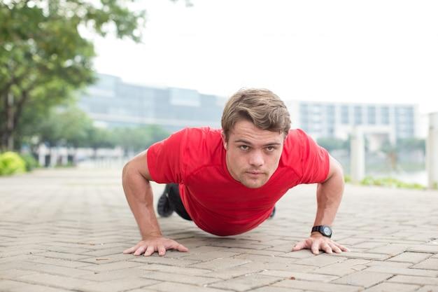 Bepaalde sportieve man die push-ups op pavement doet
