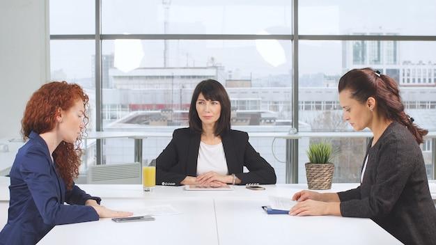 Bepaalde zakenpartners die zakelijke documenten actief bestuderen aan houten vergadertafel