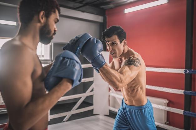 Bepaling. jonge mannen vechten op een boksring en zien er vastberaden uit