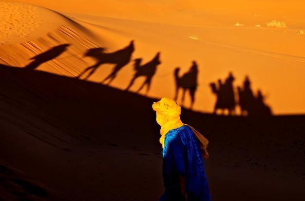 Berber op zijn rug die naar de schaduwen van een karavaan van toeristen loopt die op een kameel wordt opgezet