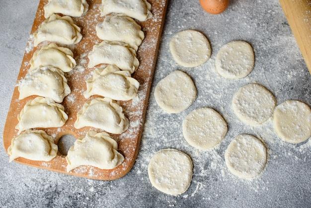 Bereid deeg en productie van cirkels uit deeg voor de bereiding van dumplings met een vulling. het kan als achtergrond worden gebruikt