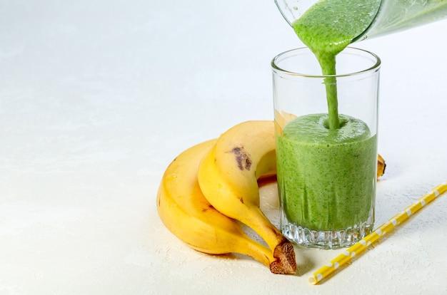 Bereid gezonde detoxdrank in een blender een smoothie gemaakt van bevroren spinazie, bananen en havermelk wordt in een glas gegoten. concept van een gezonde levensstijl