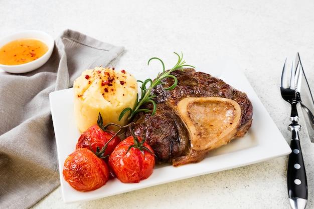 Bereide biefstuk osso bucco met aardappelpuree en tomaten