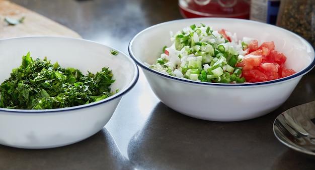 Bereide ingrediënten basilicum, groene uien en tomaten, gehakt in saladekommen