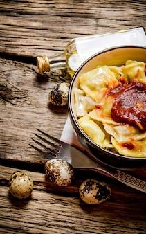 Bereide ravioli met tomatensaus in een kopje. op houten tafel.