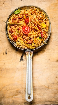 Bereide spaghetti in tomatensaus met kruiden in de pan op houten achtergrond