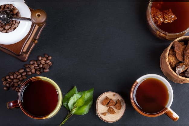 Bereiding chaga paddenstoelenkoffie. bekers, pot met chaga drankje, koffiemolen, chaga stukken en koffiebonen op zwart.