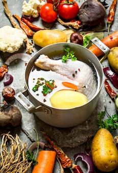 Bereiding van geurige kippensoep met verse groenten op stenen tafel.