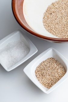Bereiding van gomashio (gomasio - sekihan kruiden) met sesamzaad en zout in suribachi (japanse streepmortel)