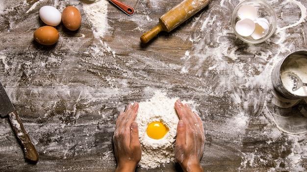 Bereiding van het deeg. de handen en gereedschappen van de deegvrouwen - zeef, deegroller, mes, garde. op een houten tafel. bovenaanzicht