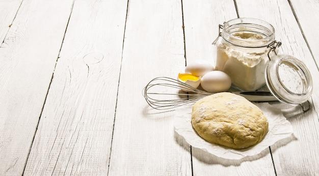 Bereiding van het deeg. het bereide deeg met de ingrediënten - eieren, bloem, zure room en garde. op een witte houten achtergrond. vrije ruimte voor tekst.