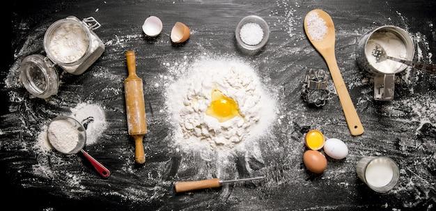 Bereiding van het deeg. ingrediënten voor het deeg - meel, eieren en gereedschap - deegroller, zeef, garde. op een zwarte houten achtergrond. bovenaanzicht
