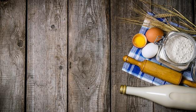 Bereiding van het deeg. ingrediënten voor het deeg - melk, bloem, eieren en deegroller. op een houten tafel. vrije ruimte voor tekst. bovenaanzicht