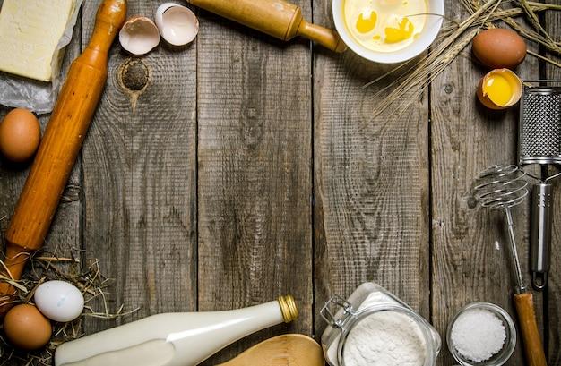 Bereiding van het deeg. ingrediënten voor het deeg - melk, bloem, eieren en verschillende gereedschappen. op een houten tafel. vrije ruimte voor tekst. bovenaanzicht