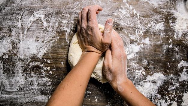 Bereiding van het deeg. voorbereiding van het deeg de handen van de vrouw. op een houten tafel. bovenaanzicht