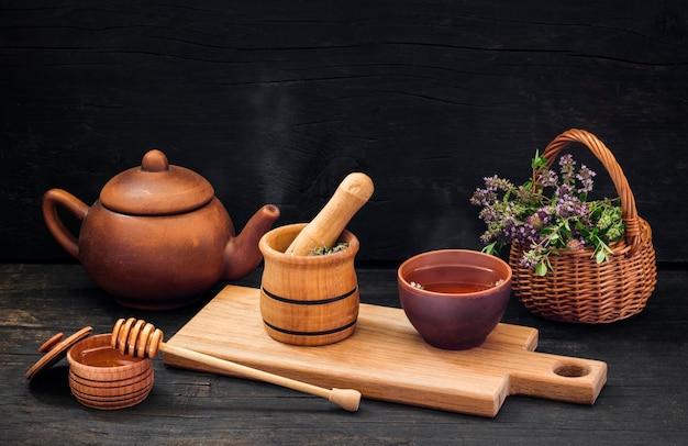 Bereiding van hete geneeskrachtige thee, van tijm en honing op een zwarte houten ondergrond