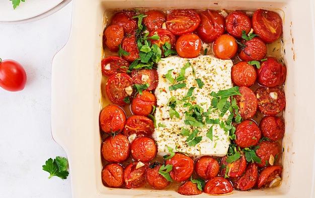 Bereiding van ingrediënten voor fetapasta. trending feta bake pasta recept gemaakt van cherrytomaatjes, feta kaas, knoflook en kruiden. bovenaanzicht, hierboven, kopieer ruimte.