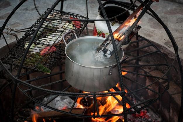 Bereiding van soep en vis op de brandstapel