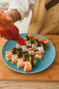 Bereiding van sushibroodjes door een professionele chef-kok bovenaanzicht knijpsaus op een set sushibroodjes