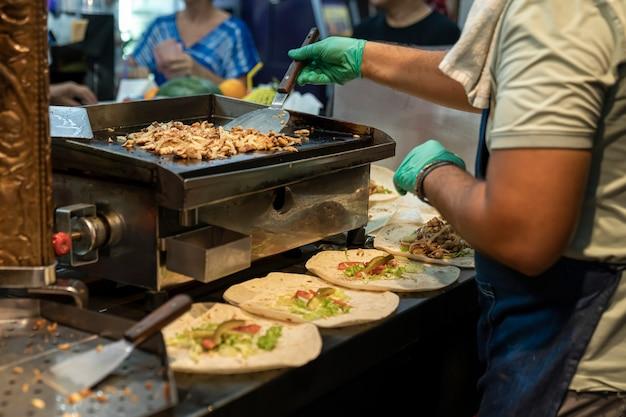 Bereiding van turkse shoarma de koks handen in rubberen handschoenen brengen een heerlijke gehakte gebakken chi ...