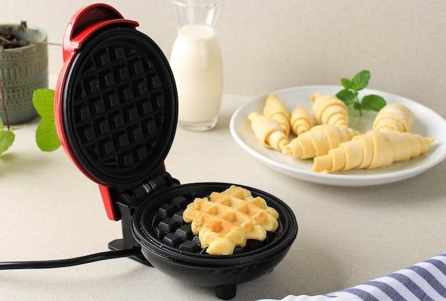 Bereidingsproces croissantwafel of croissantwafel maken van bevroren croissantdeeg met behulp van een elektrisch wafelijzer