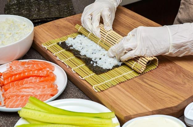 Bereidingsproces voor sushi. vrouwenhanden in rubberen handschoenen wikkelen rollen voor sushi, sushi thuis
