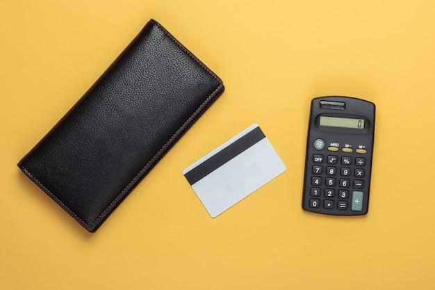 Berekening van het gezinsbudget, berekening van de kosten. portemonnee en bankkaart, rekenmachine op geel.