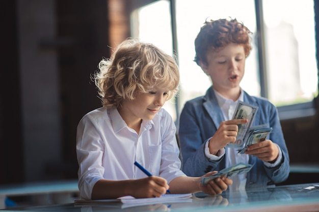 Berekeningen. twee jongens die geld tellen en aantekeningen maken