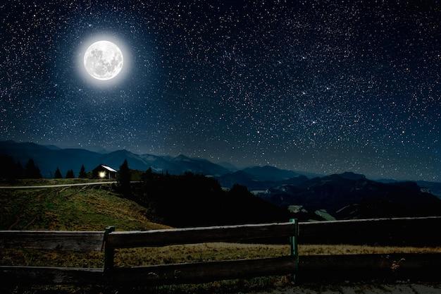 Berg. achtergronden nachtelijke hemel met sterren en maan en wolken