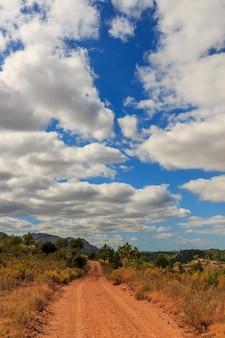 Berg onverharde weg met grote wolken natuur elementen concept