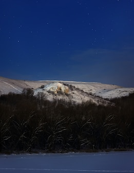 Berg 's nachts verlicht met het licht van de volle maan. foto genomen in de winter in rusland.