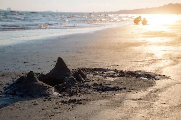 Berg van zandkasteelspel op oceaanstrand
