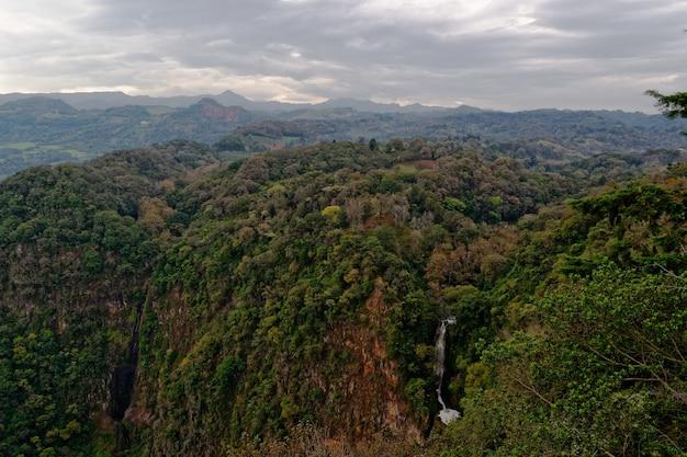 Bergachtig bos met overdag een waterval