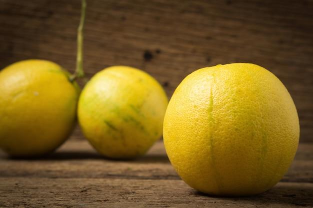 Bergamot-sinaasappels kleuren geel op roze hout