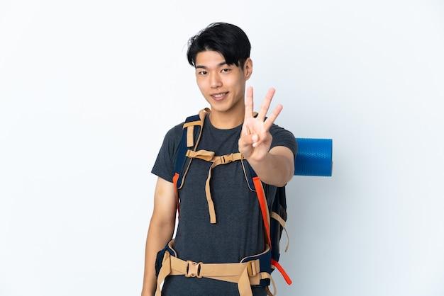 Bergbeklimmer chinese man met geïsoleerd op witte achtergrond gelukkig en drie met vingers tellen