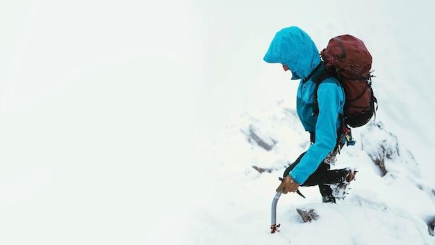 Bergbeklimmer die een ijsbijl gebruikt om forcan ridge te beklimmen in glen shiel, schotland