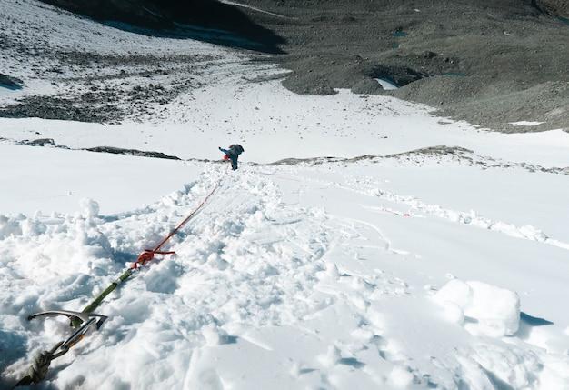 Bergbeklimmer die onderaan de verticale muur dalen. klimtoestellen. besneeuwde bergpas