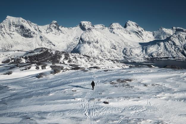 Bergbeklimmer man wandelen op sneeuw heuvel met bergketen op het eiland senja, noorwegen