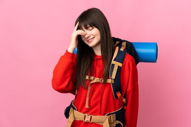 Bergbeklimmer meisje met een grote rugzak geïsoleerd op roze lachen