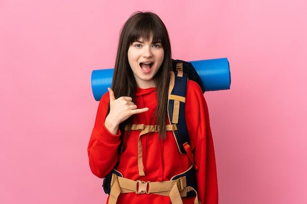 Bergbeklimmer meisje met een grote rugzak geïsoleerd op roze telefoongebaar maken
